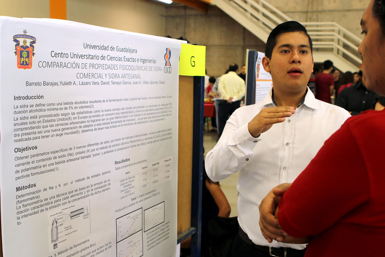 Estudiante explica en carteles la Expo Ciencia de los Alimentos en CUCEI