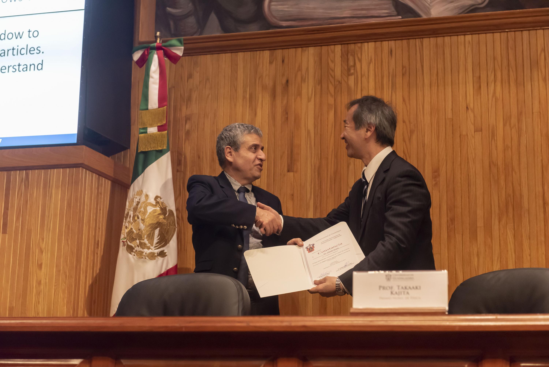 Le entrega el Vicerrector un documento de reconocimiento al Premio Nobel por su participación