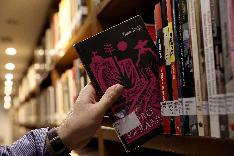 La imagen de una mano jalando el libro de Pedro Páramo de Juan Rulfo en la Biblioteca