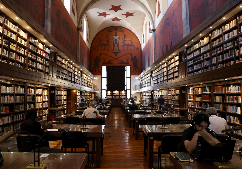 Panorámica de la Biblioteca Iberoamericana, donde se muestran los murales, los libros y lectores leyendo