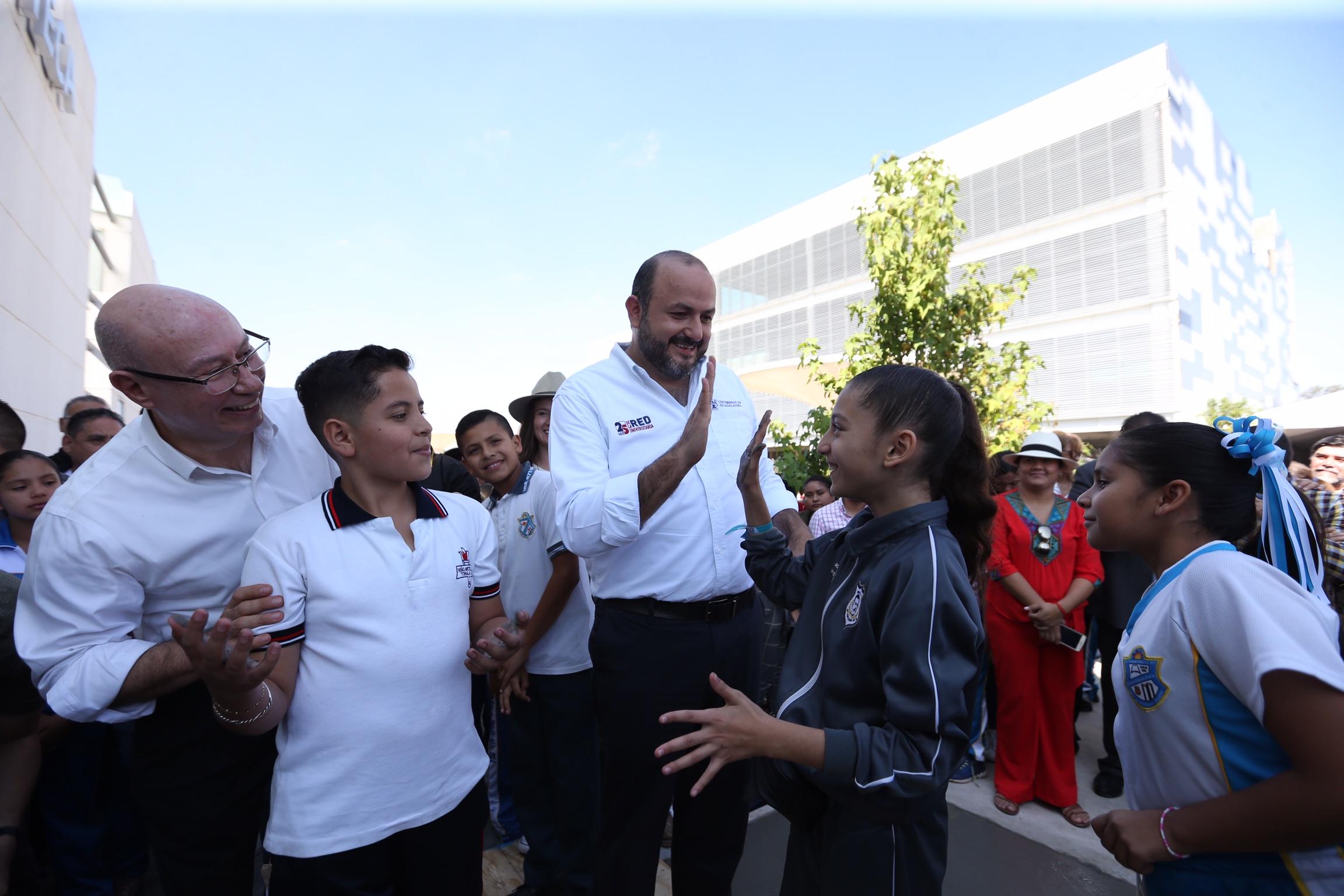 Choca las palmas de las manos el Rector General con dos niños que asitieron al festival