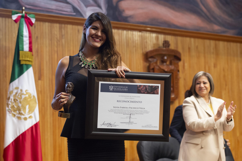 Silvia Fabiola Pacheco Villa muestra a la camara su reconocimiento despues de su entrega