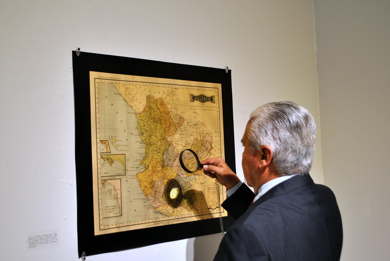 Persona examinando los mapas con una lupa