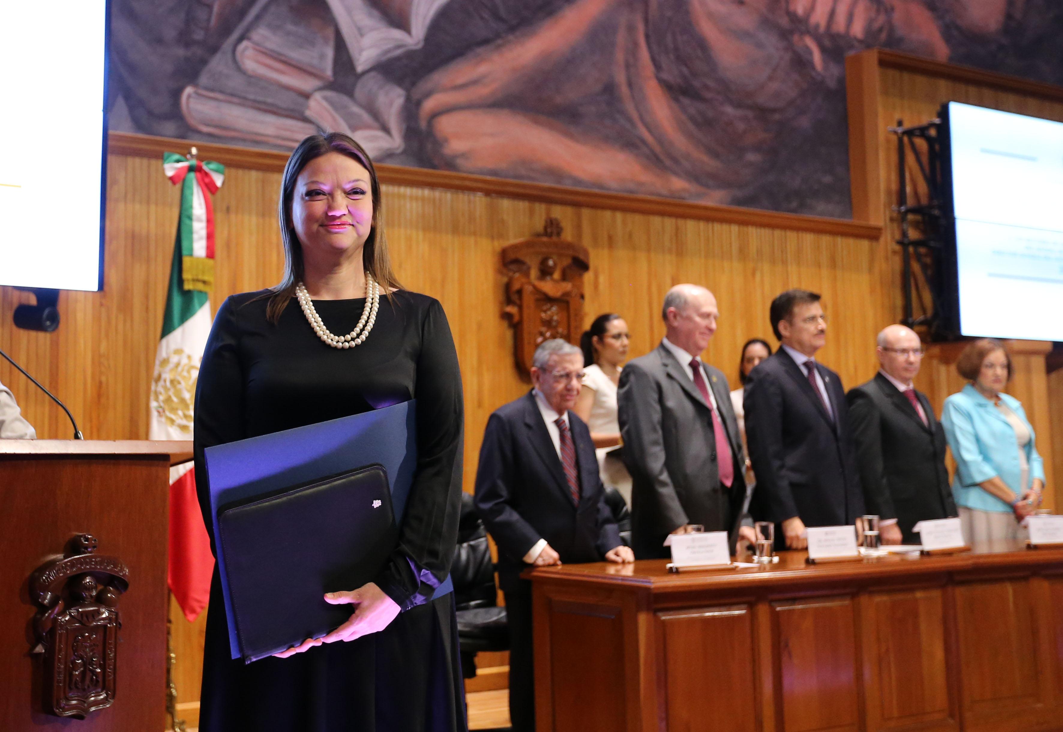Maestra María Felícitas Parga Jiménez,  mostrando la carpeta de su  nombramiento, donde se le rectifico como Rectora del centro universitario del CUCiénega.