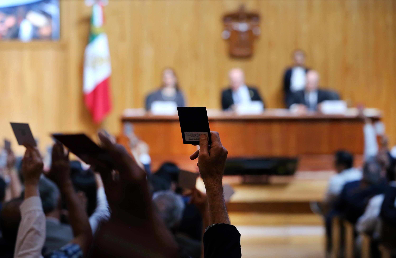 Un consejero universitario levantando su voto durante la sesión del Consejo General Universitario