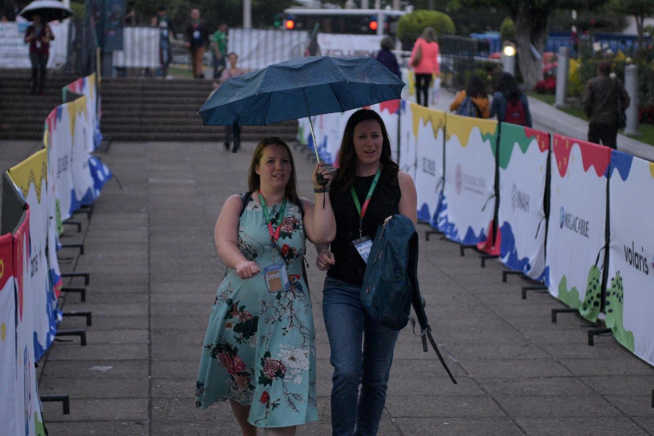 Expositoras del país invitado a la FIL, con paraguas abierto en mano, protegiendose de la lluvia, mientras recorren el pasillo de la explanada para entrar a instalaciones de la Expo.