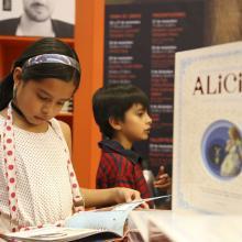 Niña leyendo un libro durante la FIL, en un área exclusiva para público infantil.