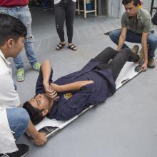 Estudiantes del CUAAD, probando una camilla de rescate fabricada.