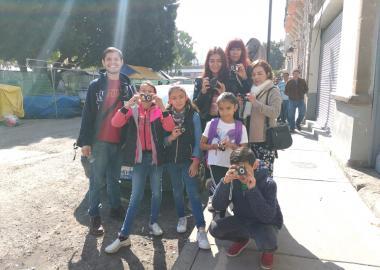Un grupo de jóvenes y niños de diversas edades, con cámaras fotográficas em mano.