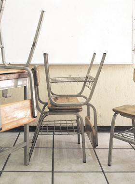 Mesabancos viejos y maltratados amontonados frente al pizarrón de un salón