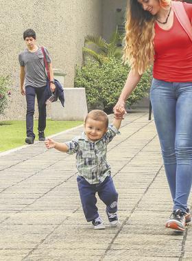 Mujer sosteniendo con la mano a un niño para ayudarle a caminar