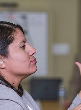 Persona con problemas de audición, comunicandose a través de señas con las manos