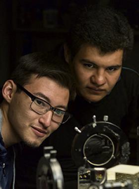Jóvenes estudiantes observando el funcionamiento de un equipo mecánico y tecnológico.