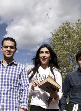 Estudiantes universitarios caminando por los pasillos del jardín de la escuela y llevando libros bajo el brazo.