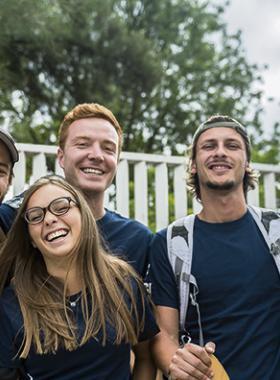 Grupo de estudiantes extranjeros, a las afueras de los jardines de un centro universitario.