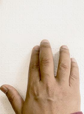 Mano de persona leyendo en braille